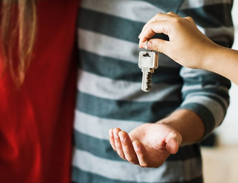 Person's hand handing over keys